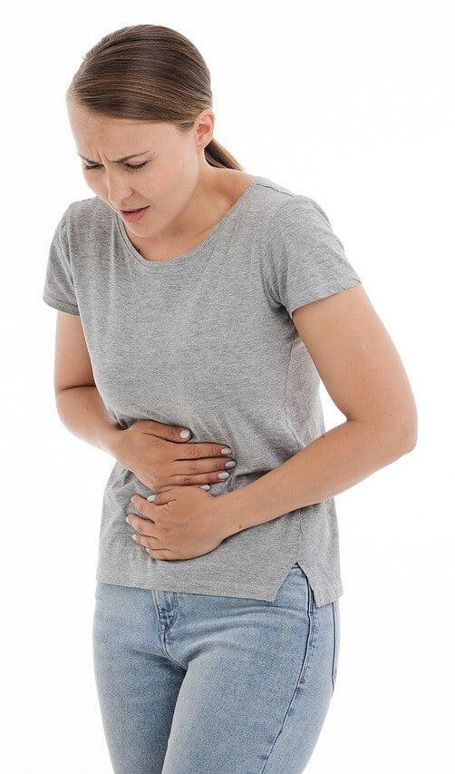 Slika prikazuje žensko v bolečinah, ki se drži za želodec - Mastikina smola lahko pomaga odpraviti želodčne težave