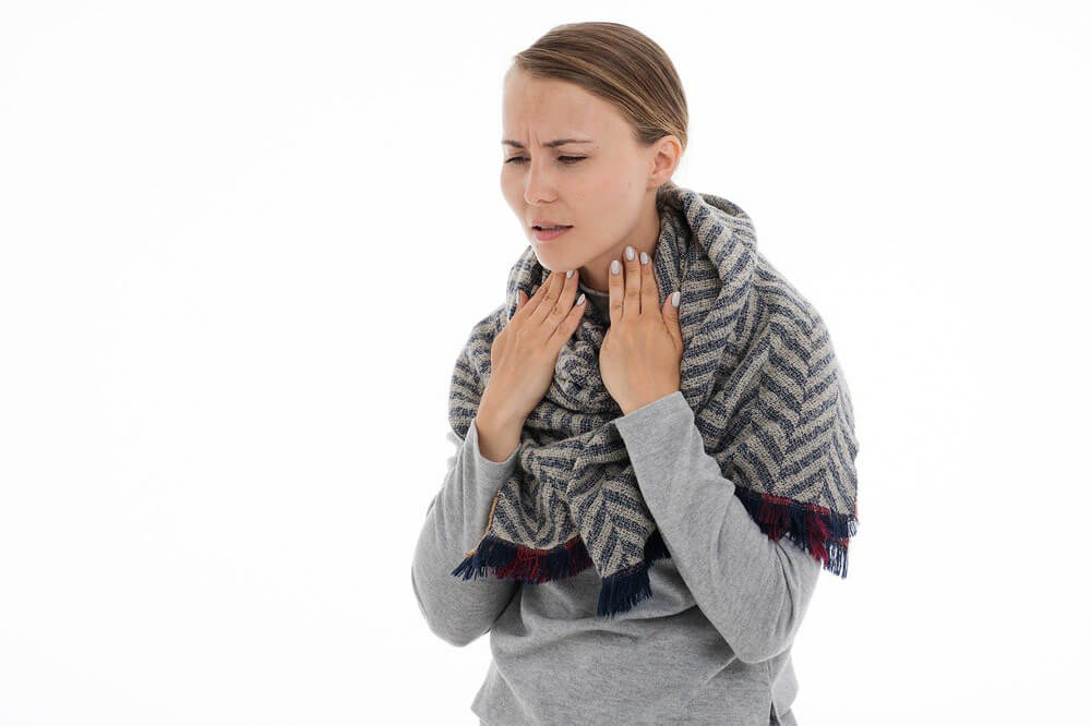 Slika prikazuje žensko z vnetim grlom za članek z naravo nad vneto grlo.
