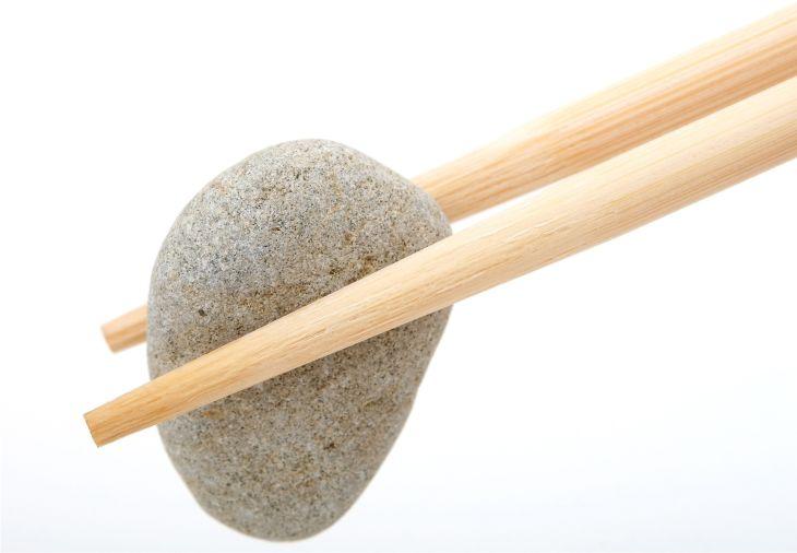 Mastika slika prikazuje manjši kamenj ki ga držita dve palčki za članek bolečine v želodcu.