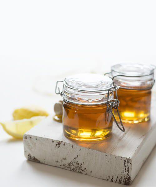 Na sliki sta prikazana dva kozarca medu v ozadju vidimo tudi rezino limone, med je postavljen na leseno desko. Slika se uporablja za članek Helicobacter pylori.