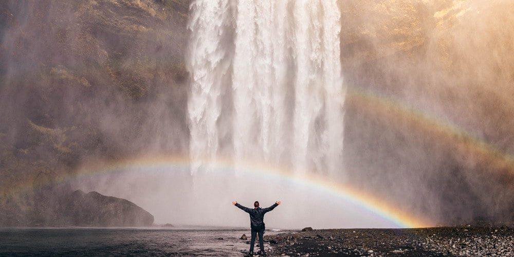 Na sliki je moški, ki stoji pred slapom z raztegnjenimi rokami, pred slapom ki ga gleda sta tudi dve mavrice.