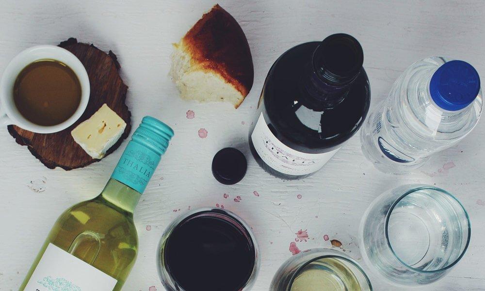 Na sliki so steklenice vina ter šalčke kave, za blog tiščanje v želodcu.