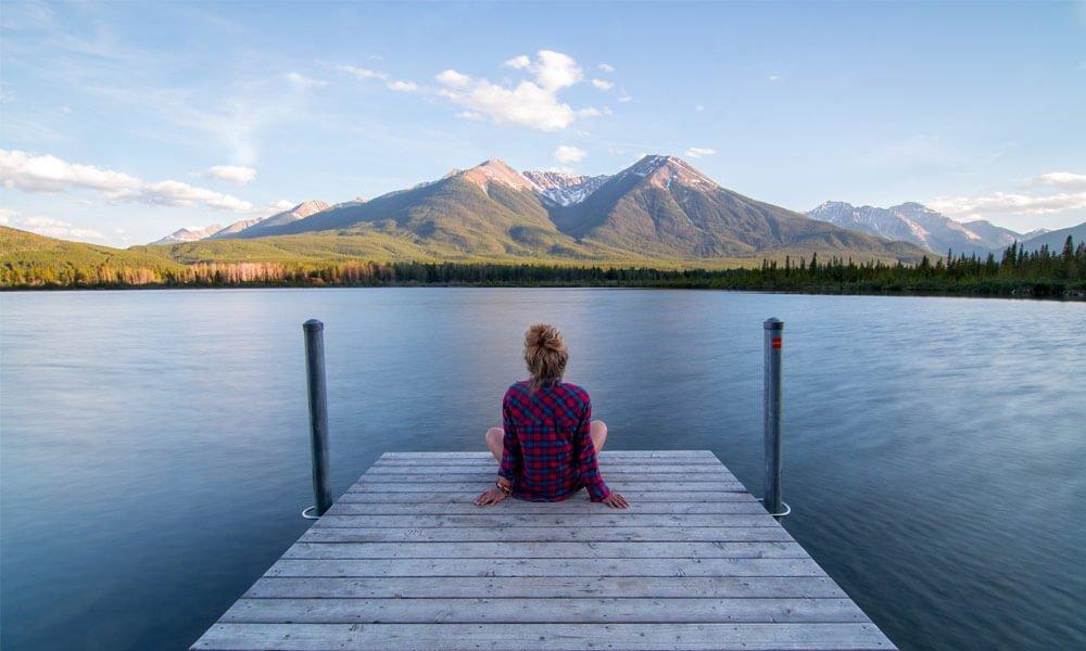 Slika prikazuje dekle na manjšem lesenem pomolu, ki gleda proti goram.