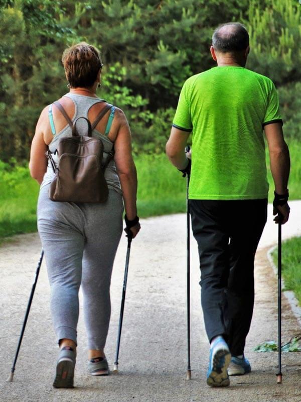 Na sliki sta dve starejše osebe, ki skupaj športata v naravo, in hodita z pohodniškimi palicami.