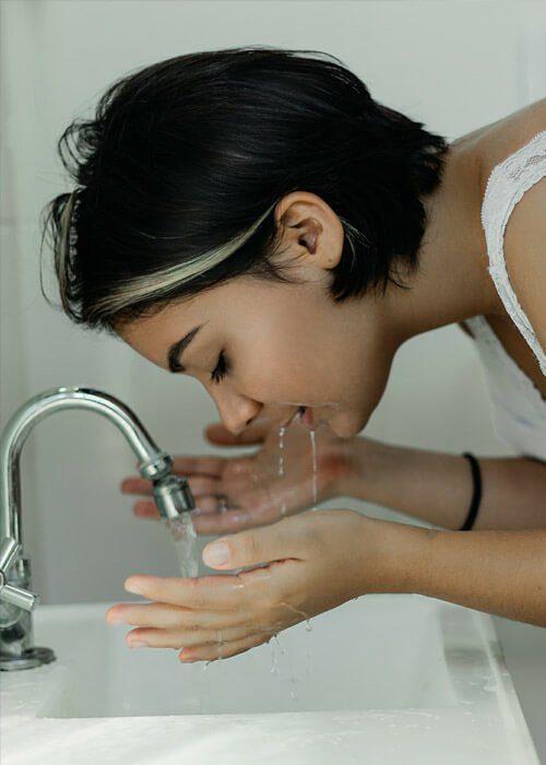 Slika prikazuje dekle, ki si umiva obraz - eterično olje.