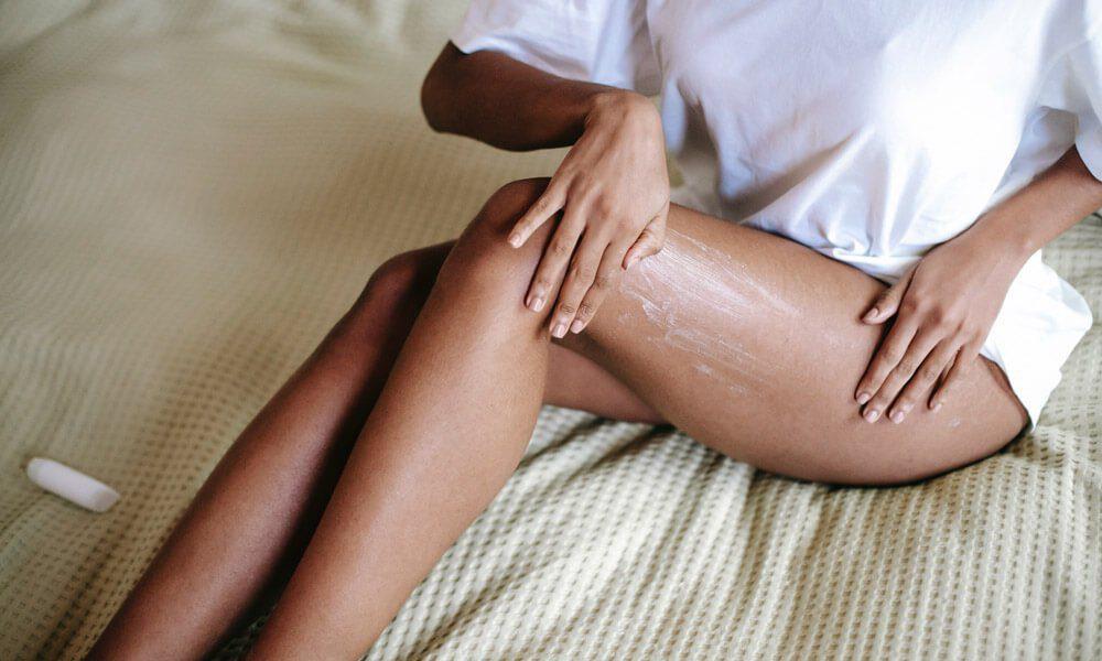 Slika prikazuje dekle, ki si maže noge z eteričnim oljem mastika (mastiha).