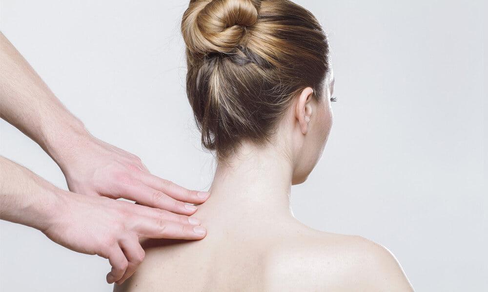 Slika prikazuje dekle ki sedi ko jo med tem nekdo pregleduje hrbtenico, navezuje se na članek sindrom razdražljivega črevesja.